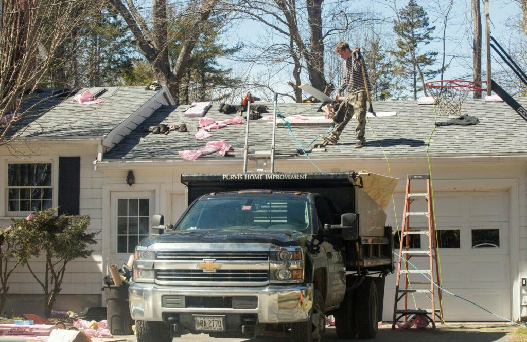 A crew from Purvis Home Improvement works on the roof of a home in Cape Elizabeth on Thursday. The owner of the Scarborough home improvement company, Shawn D. Purvis, faces manslaughter charges in the death of a roofer who fell from a roof on Munjoy Hill in Portland in December.
