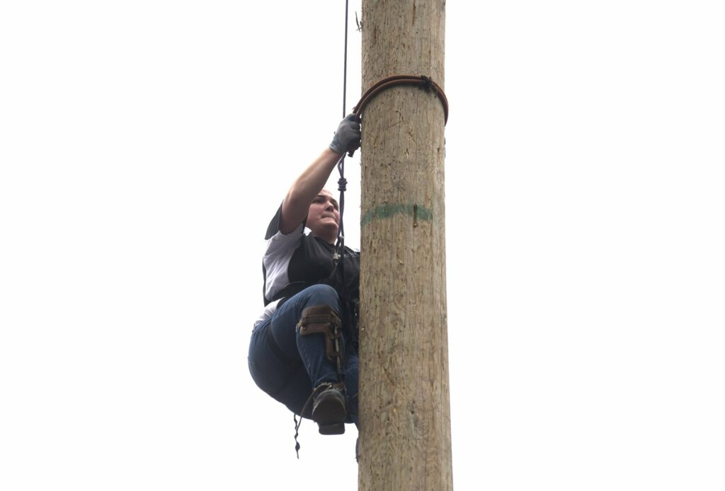 The University of Maine's Abigail Weckesser lowers herself from the top of a 40-foot-high wooden pole Saturday during the pole climbing competition at the annual Woodsmen's Mud Meet at Colby College in Waterville.