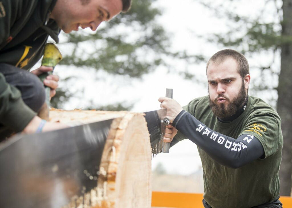 Unity College's Brodie Holmes competes Saturday in the single-person crosscut competition at the annual Woodsmen's Mud Meet at Colby College in Waterville.