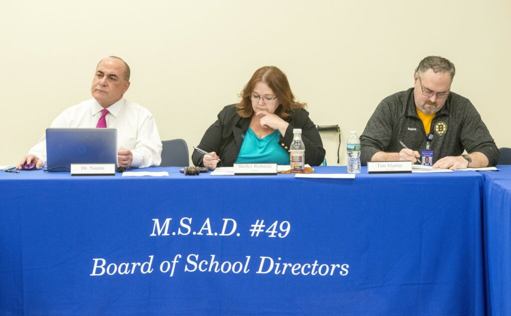 Reza Namin, superintendent of MSAD 49, left, Shelley Rudnicki, school board chair, center, and Tim Martin, vice chair, right,  listen to school board member Kara Kugelmeyer voice her concerns about changes in legal counsel during a board meeting at Lawrence Junior High School in Fairfield on Thursday.