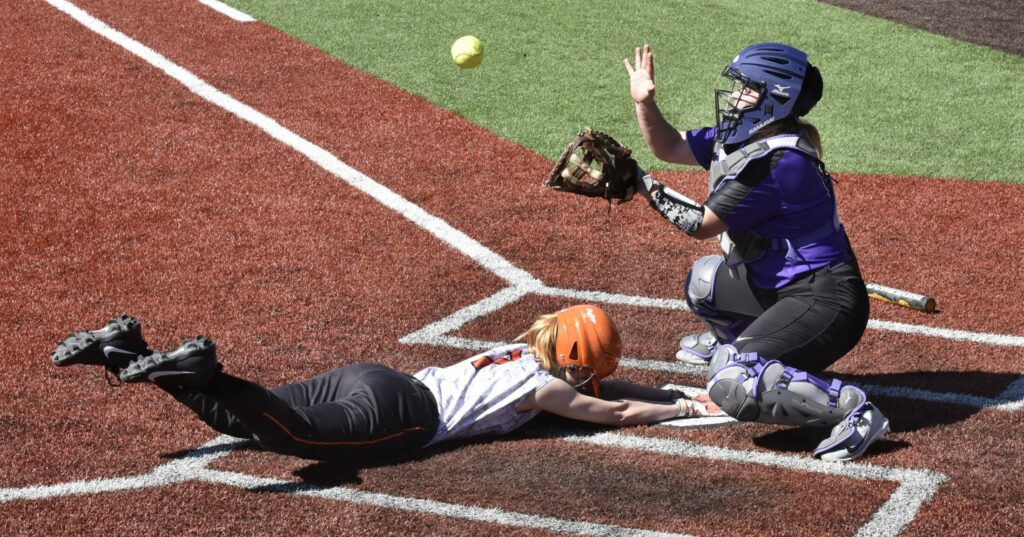 Winslow's Katie Bailey slides safe into home as Waterville catcher McKayla Nelson reaches for ball on Wednesday.