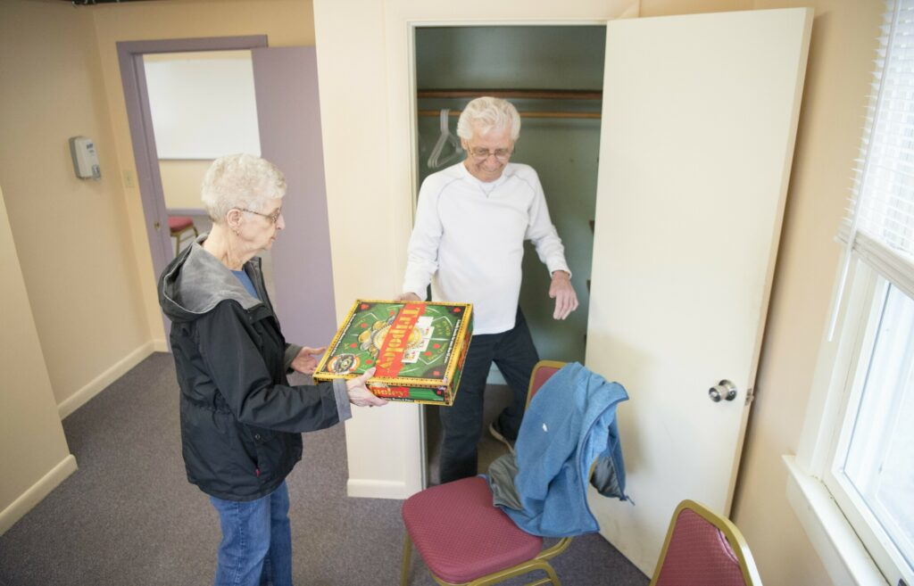 Pauline Matthieu hands games to Chuck Pare to be put away at the Oakland Senior Center. The center at 47 Heath St. in Oakland will host an open house Tuesday from 10 a.m. to noon.