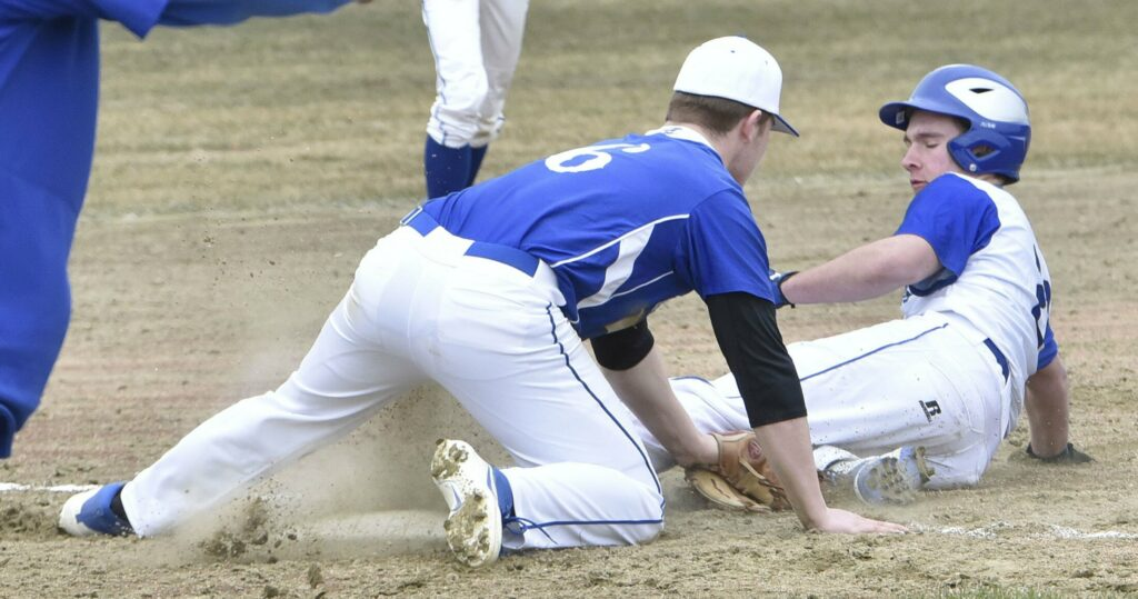 Erskine's Joe Clark tries to tag Lawrence baserunner Mike Roy during a close play at third base Thursday in Fairfield. Roy was called safe on the play.