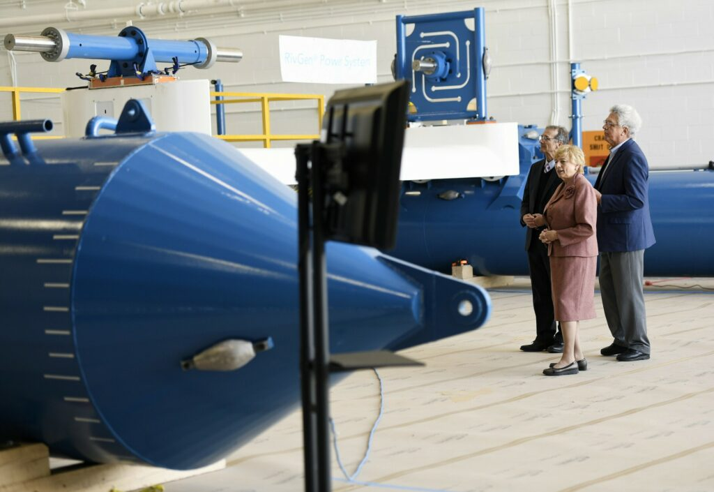 Gov. Janet Mills gets a tour of Ocean Renewable Power Co.'s RivGen Power System at Brunswick Landing in April. Giving the tour are company executives John Ferland, left, and Christopher Sauer. The company was celebrating the commercial launch of the system, which generates electricity from submerged turbines in rivers.