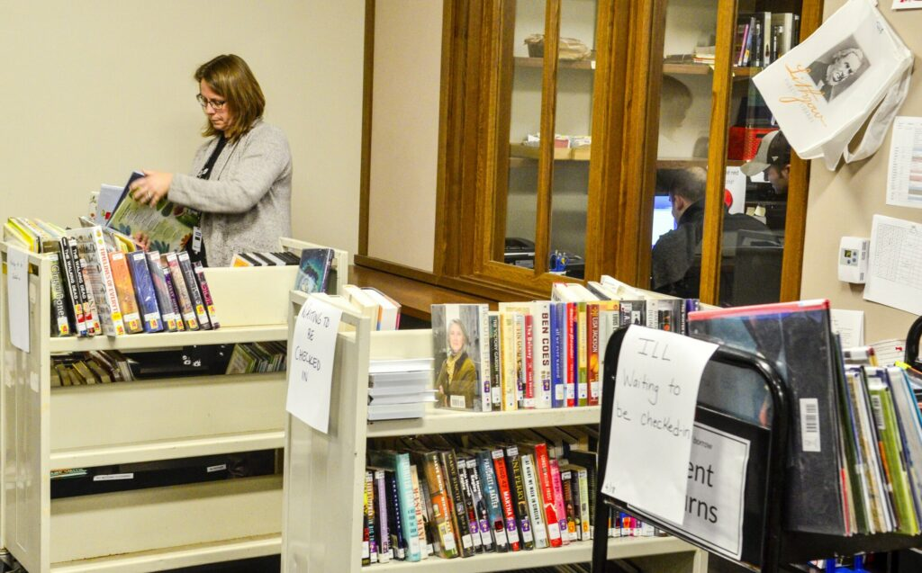 Librarian Kellie Dudley sorts books onto carts Thursday at Lithgow Public Library in Augusta so they can be scanned back in after the circulation computer system is fixed.
