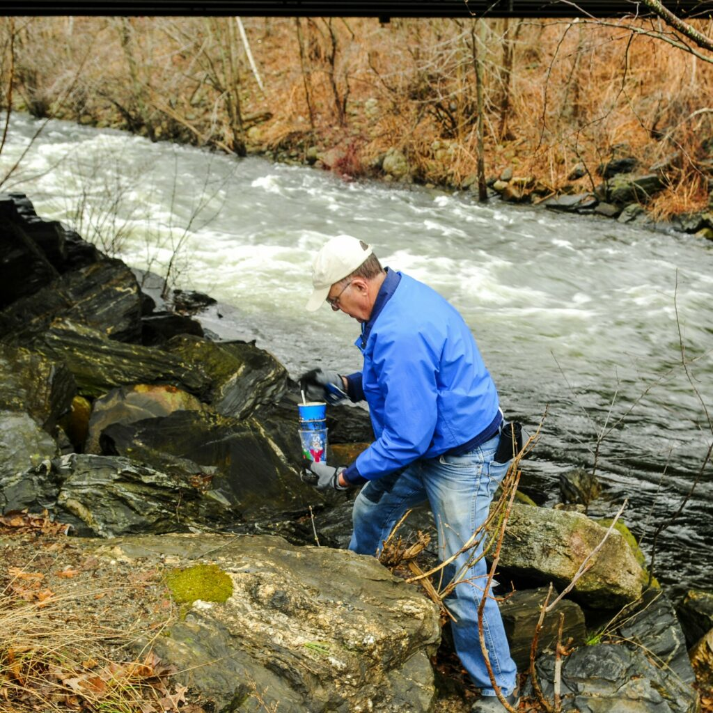 Bob Simpson picks up trash along the banks of Cobbosseecontee Stream in Gardiner. He was part of a group doing the cleanup for Earth Day.
