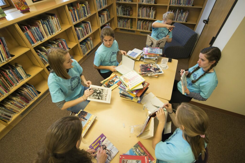 Colby College students refurbish books Saturday at Waterville Public Library as part of Colby Cares Day activities.