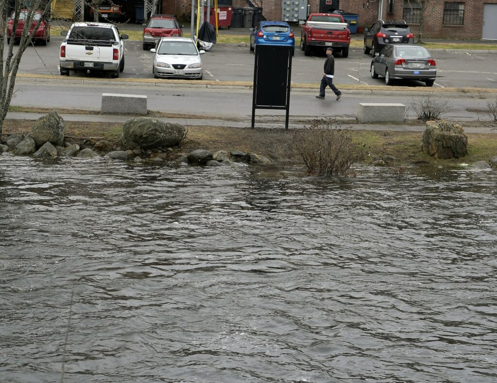 The swollen Cobbosseecontee Stream rises up the banks Sunday to the edge of a parking lot in downtown Gardiner.