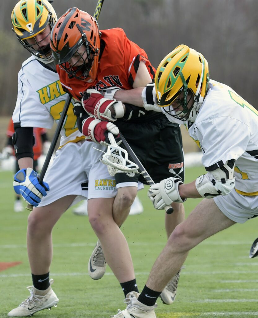 Maranacook/Winthrop/Spruce Mountain teammates Will Colvin, left, and Jacob Sousa sandwich Winslow's Jared Lambert during a lacrosse game Monday at Kents Hill School.