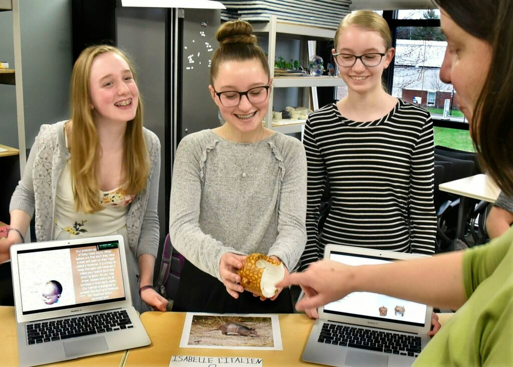 Brynn Lilly, from left, Isabelle L'Italien and Lily Mitchell, students with the gifted and talented program at Messalonskee Middle School, show Brigid Mullally a human infant skull cap made with a 3-D printer that replicates armadillo armor during a biomimicry project at Thomas College in Waterville on Tuesday.