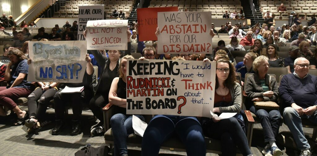 SAD 49 students hold signs up in the front row toward school board members and Superintendent Reza Namin during a well attended meeting with students, faculty and parents in Fairfield on Thursday.