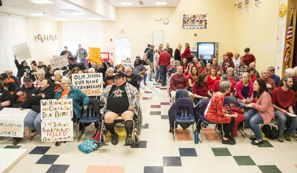 "Supporters of the ""Indians"" nickname wear black on the left, and those in favor of removing it wear red on the right as they wait for the beginning of a school board meeting in April on a proposed nonbinding referendum about whether to retire the name in Skowhegan."
