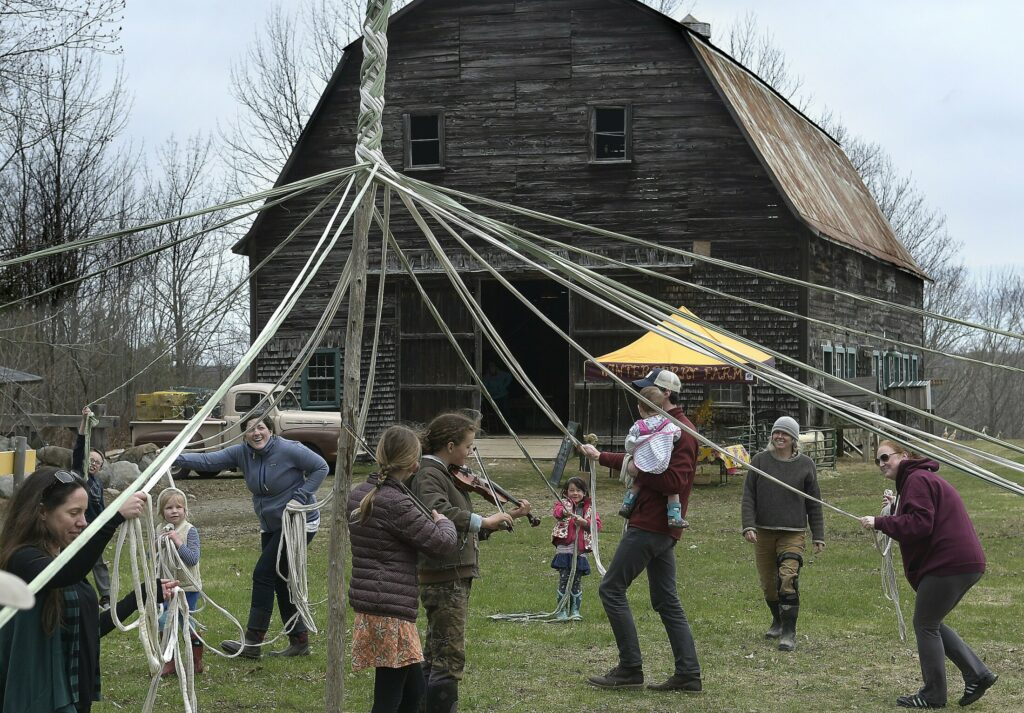 People walk around a maypole Sunday at Winterberry Farm in Belgrade.