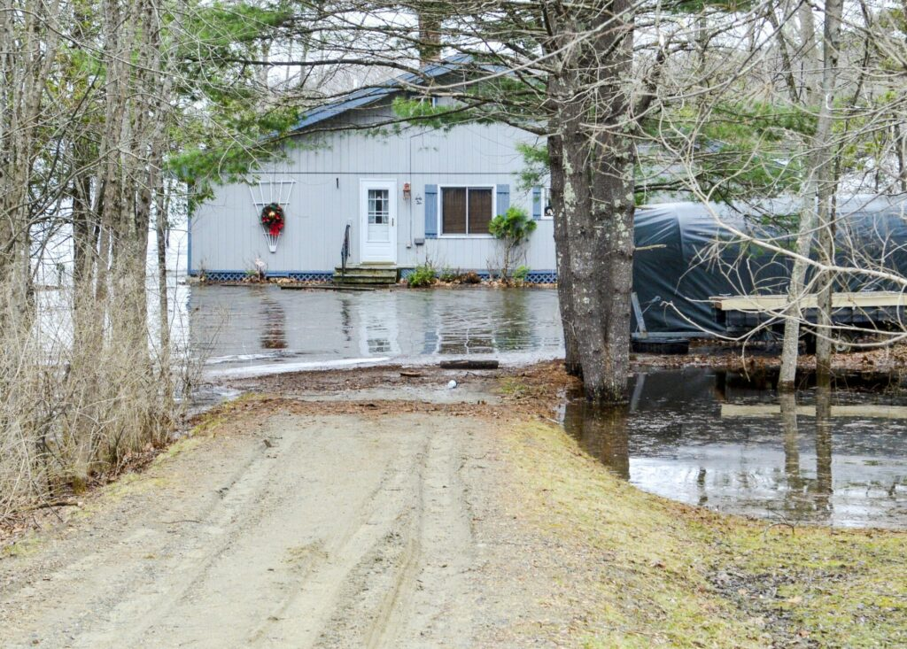 High water from Androscoggin Lake surrounds one of two homes on Route 133 near the state boat launch on Friday in Wayne.