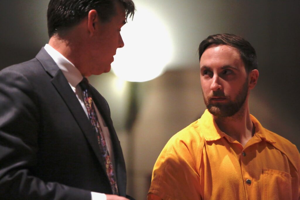 Mark Cardilli Jr., right, listens to his attorney, Jon Gale, during a court appearance Tuesday to face a murder charge in the shooting death of Isahak Muse in Portland last month.