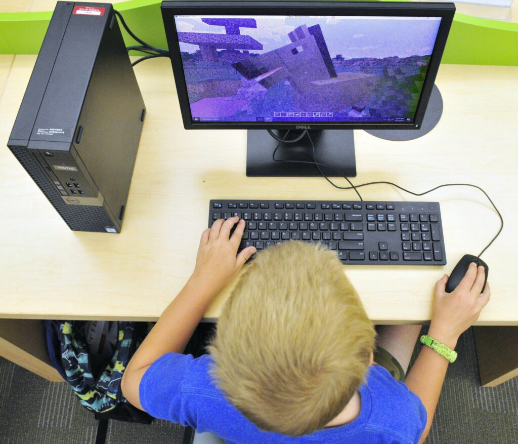 Wesley Jordan plays Minecraft on a computer in the children's area of the Lithgow Public Library on Aug. 18, 2017 in Augusta. A computer virus shut down computer systems throughout city operations two weeks ago, including at Lithgow.