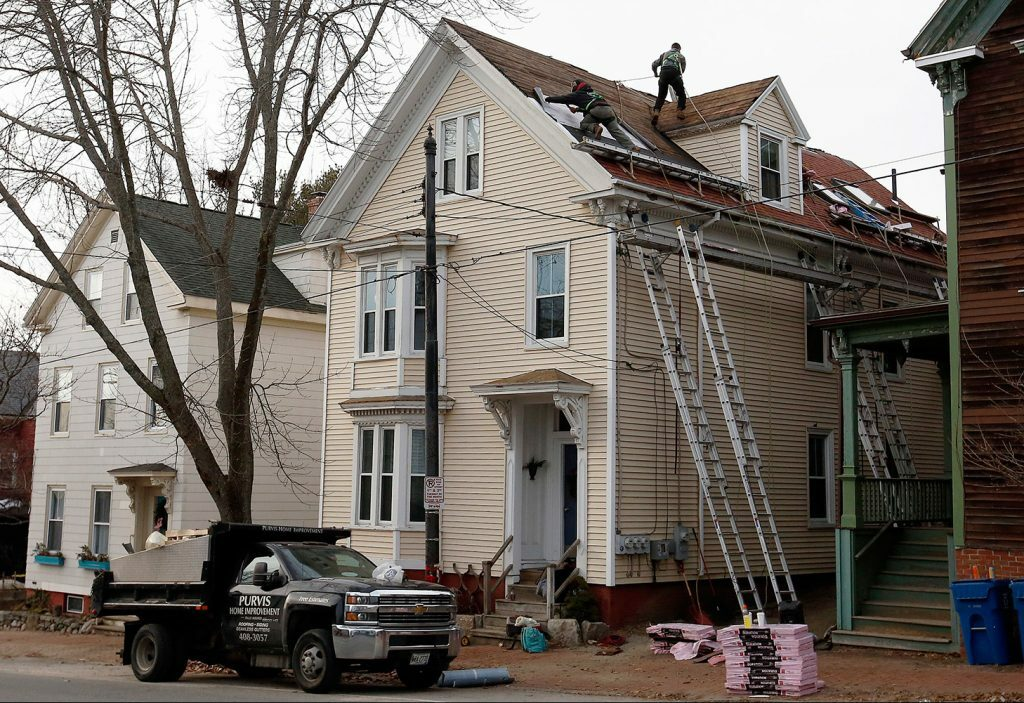 Workers from Purvis Home Improvements of Scarborough were back on the job at a home on Munjoy Hill in Portland the day after a worker died in a fall from the roof in December 2018.