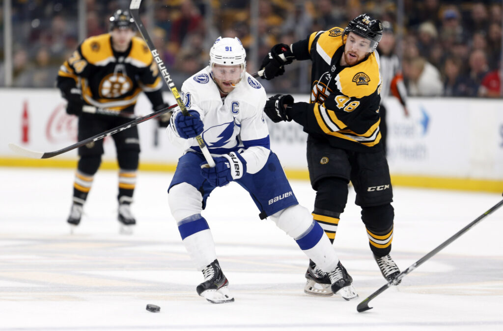 Tampa Bay's Steven Stamkos and Boston's Matt Grzelcyk battle for the puck during the first period  of the Lightning's 6-3 win Saturday in Boston.
