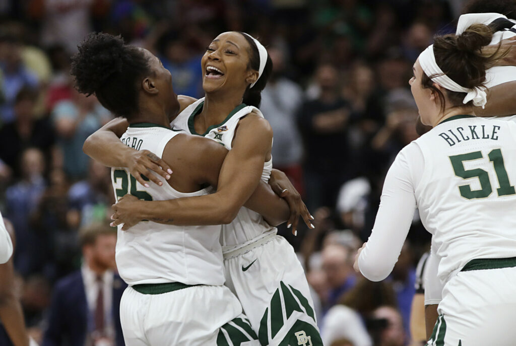 Chloe Jackson jumps into the arms of Queen Egbo after Baylor held on to beat Notre Dame, 82-81, to win the NCAA Division I title on Sunday in Tampa, Fla.