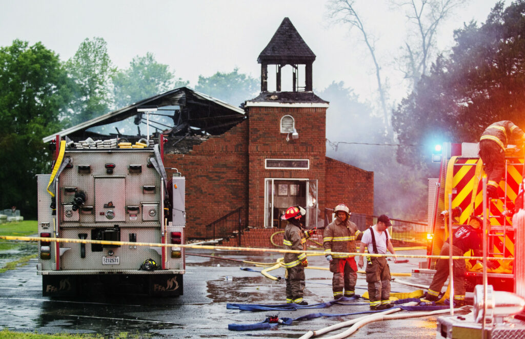 In this April 4, 2019 file photo, firefighters and fire investigators respond to a fire at Mt. Pleasant Baptist Church, in Opelousas, La. Authorities have arrested a person in connection with suspicious fires at three historic black churches in southern Louisiana, a federal prosecutor said.