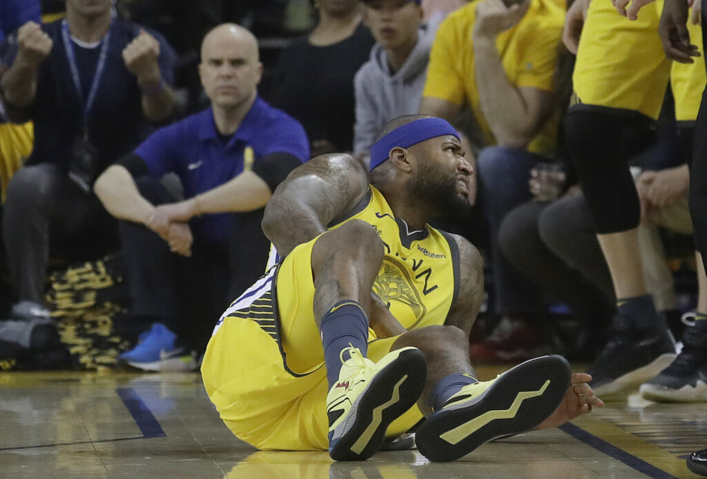 Golden State center DeMarcus Cousins reacts after falling to the floor during the first half of Monday's Game 2 loss to the Clippers. Cousing suffered a torn quadriceps muscle and is out indefinitely. (Associated Press/Jeff Chiu)