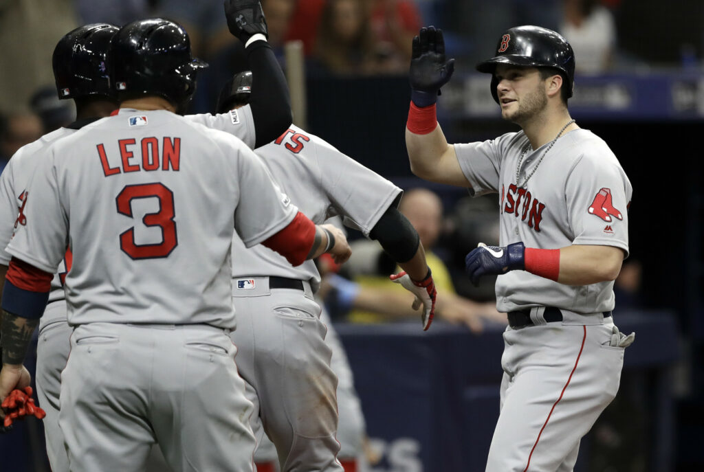 Andrew Benintendi, right, is congratulated by teammates after hitting a grand slam in the second inning Saturday against the Tampa Bay Rays. Benintendi finished with five RBI in Boston's 6-5 win.