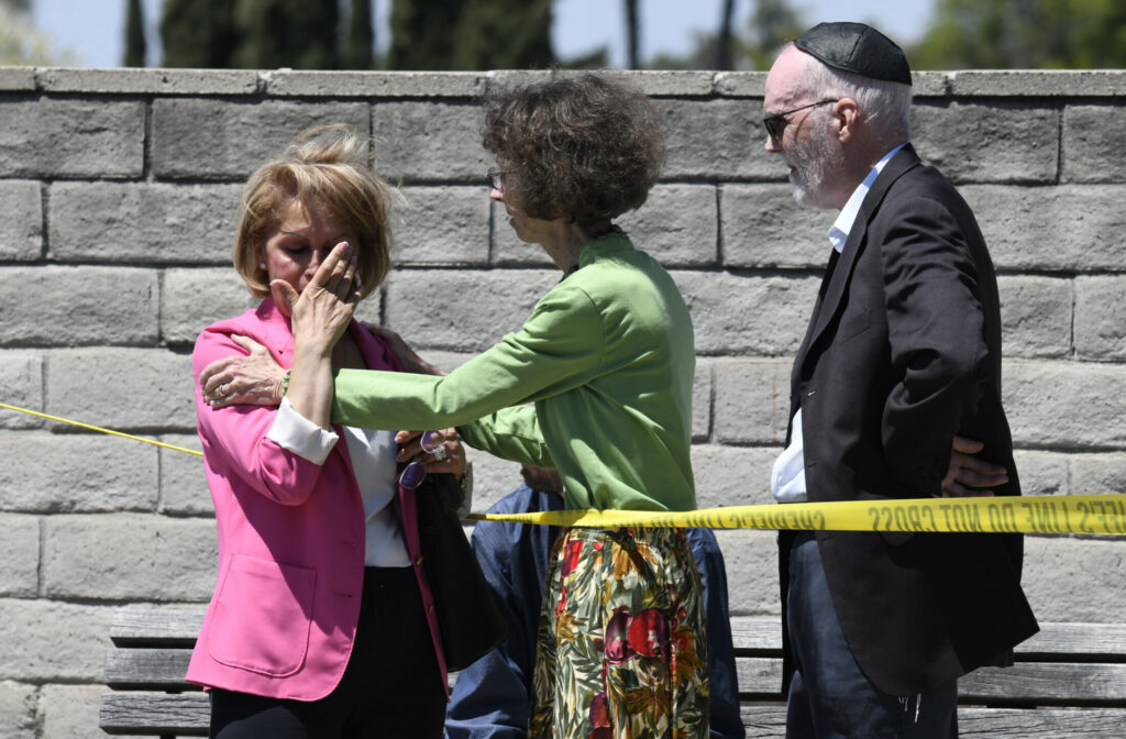 Synagogue members console one another outside of the Chabad of Poway Synagogue Saturday in Poway, Calif. Police have confirmed one is dead and three are injured.