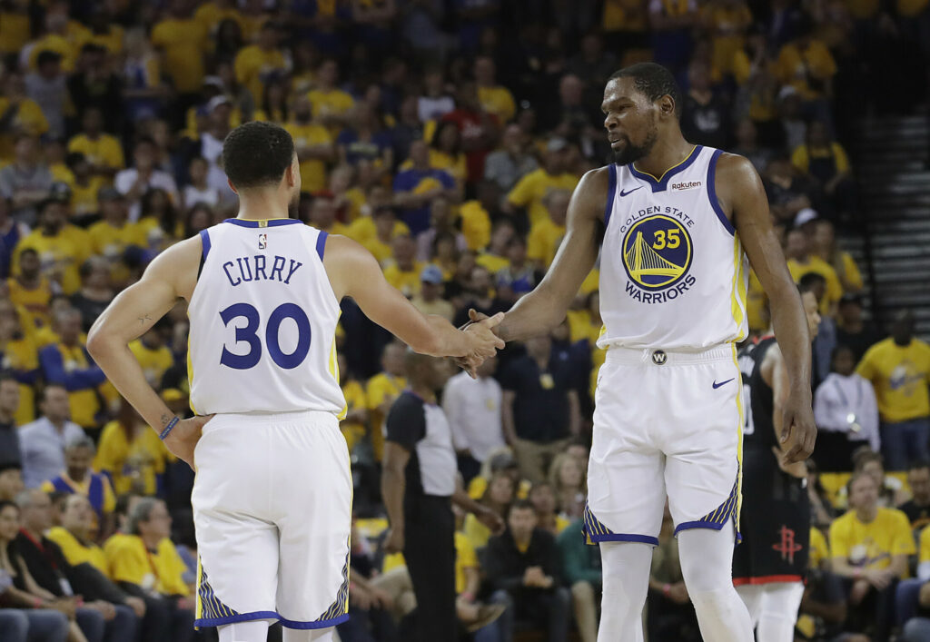 Associated Press/Jeff Chiu Stephen Curry and Kevin Durant of the Golden State Warriors celebrate Sunday during the 104-100 victory over the Houston Rockets in Game 1.