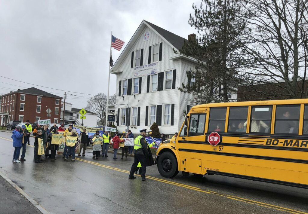 Protesters block a bus transporting guests headed to Bath Iron Works for a christening ceremony of a Zumwalt-class guided missile destroyer named for former President Lyndon Baines Johnson.  Associated Press/David Sharp
