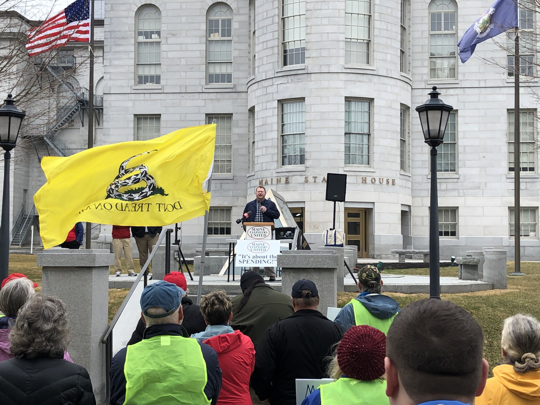 Jacob Posik, communications director for the Maine Heritage Policy Center, a right-leaning think tank that advocates for tax cuts, speaks to a crowd of about 60 at a rally against taxes at the State House on Monday – the day state and federal income taxes were due in most of the U.S.