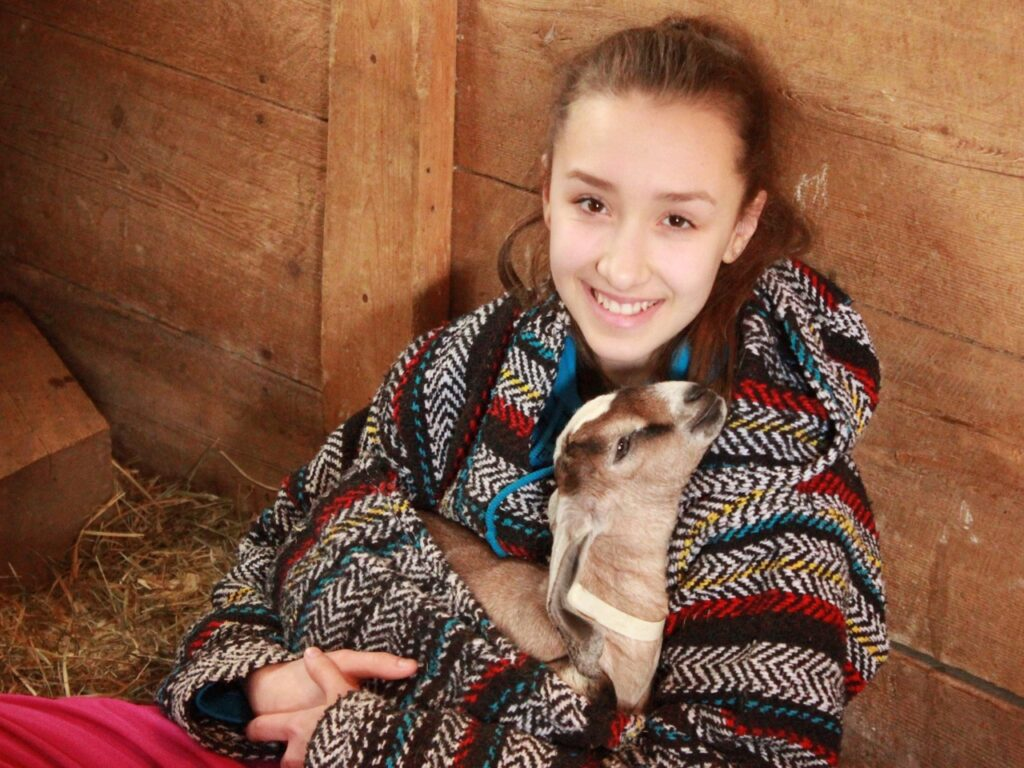 Lily Bray and Nubian goat kid Odysseus at Pumpkin Vine Family Farm in Somerville.