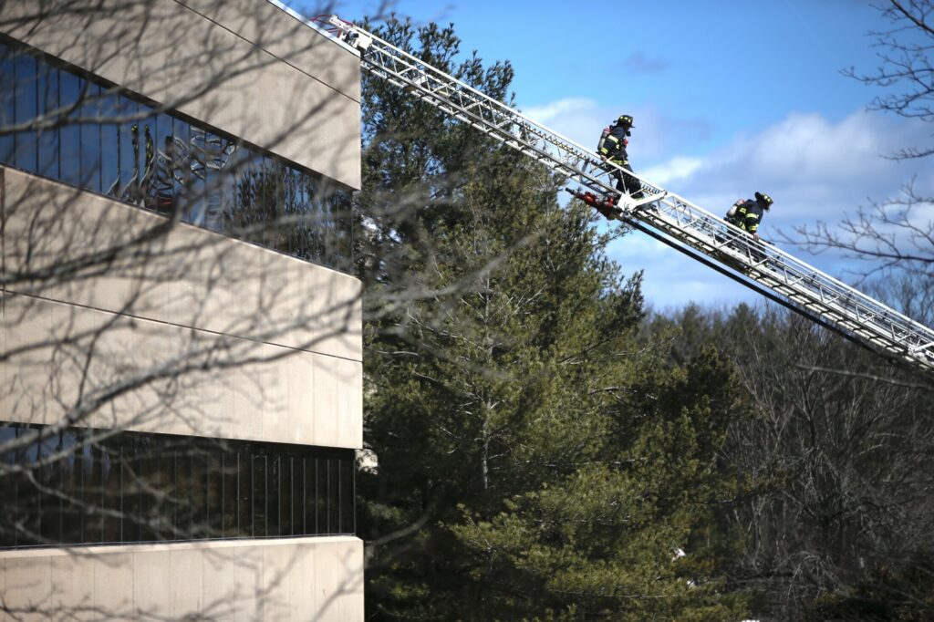 Firefighters descend a ladder from the roof of the Unum office building at 2211 Congress St. in Portland on Saturday after extinguishing a fire there.