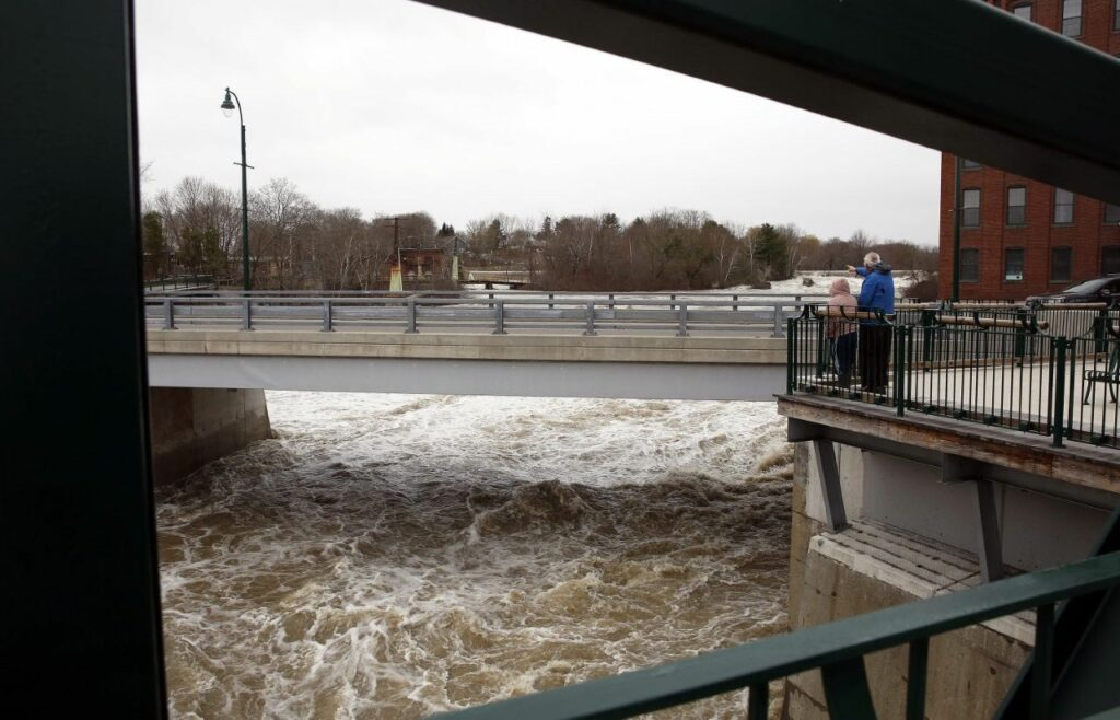 The Presumpscot River rages under Bridge Street on Saturday while Portland residents Mary DeLois and Bob Raff observe the scene.