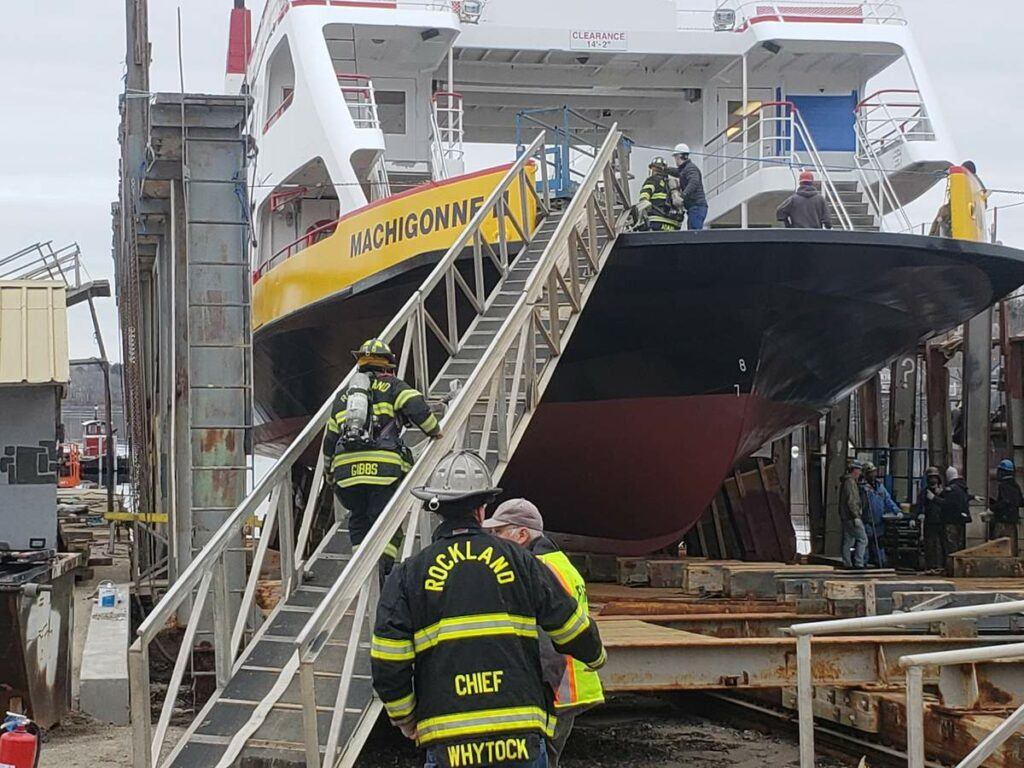 Rockland firefighters haul hoses up to the deck of a ferry at Rockland Marine.