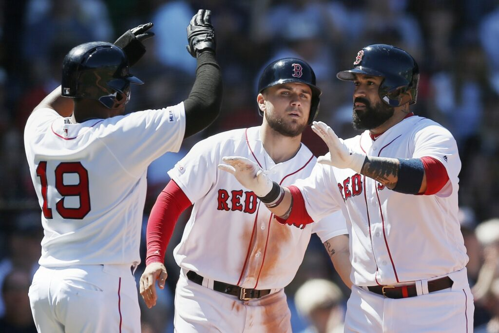 Boston's Sandy Leon, right, celebrates his three-run home run with Michael Chavis, center, and Jackie Bradley Jr. on Saturday in Boston. The Red Sox beat Seattle, 9-5.