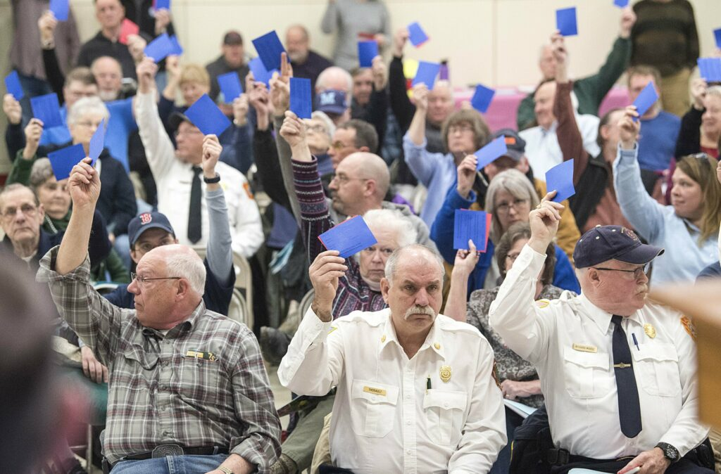 Tim Theriault, China's fire chief, front row center, and Richard Morse, right, cast their votes during the annual town meeting at the China Middle School in April 2019.