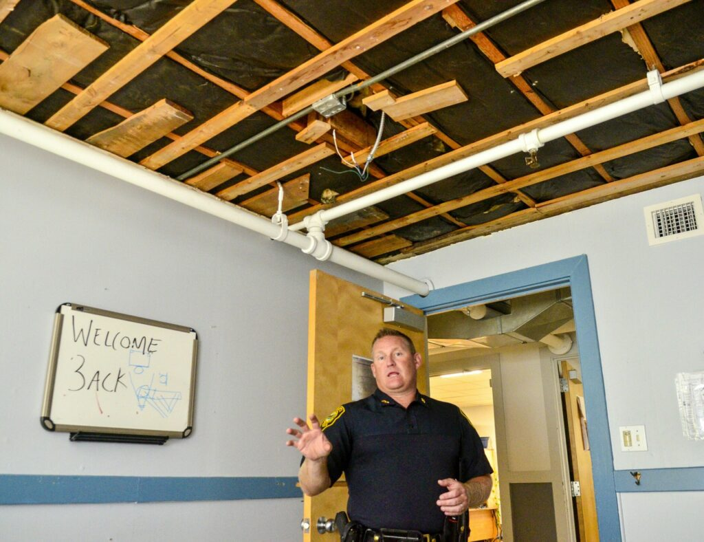 Augusta Police Chief Jared Mills stands in a detective's office, where the ceiling was ripped down after a leak, during a tour of the Augusta Police Station on Aug. 21, 2019, in Augusta. The tour highlighted reasons why the city is exploring constructing a new police station.