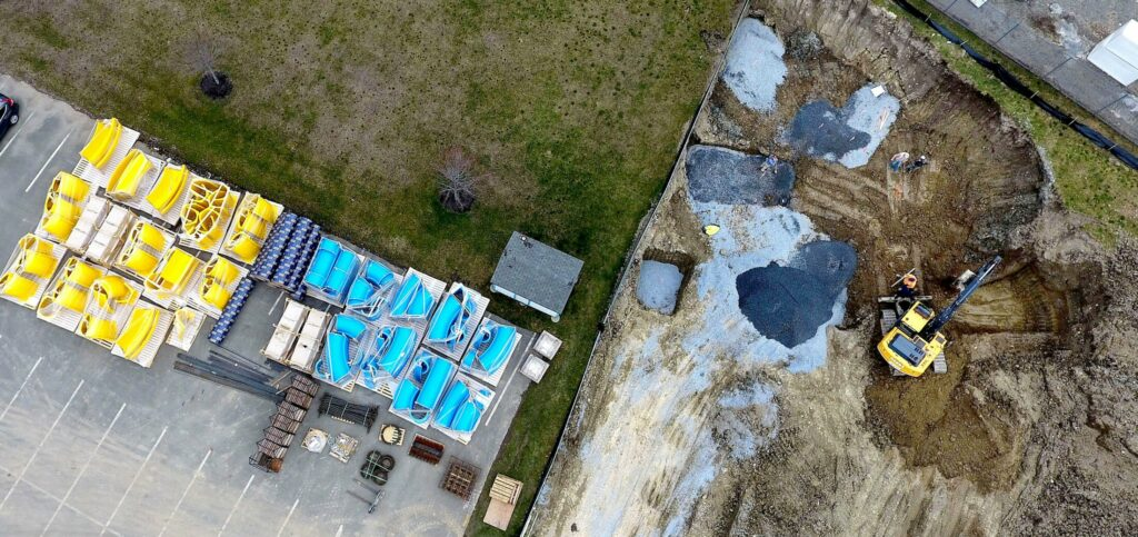 An aerial photo shows workers, right, excavating on Wednesday the area where the new water slide, blue and yellow pieces to the left, will be erected at the Alfond Municipal Pool complex in Waterville. The pool is scheduled to open June 15.