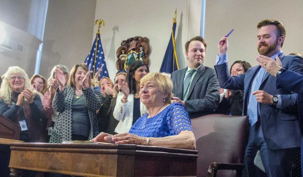 Dozens of House and Senate co-sponsors cheer after Gov. Janet Mills signed into law a bill banning the practice of conversion therapy in Maine.