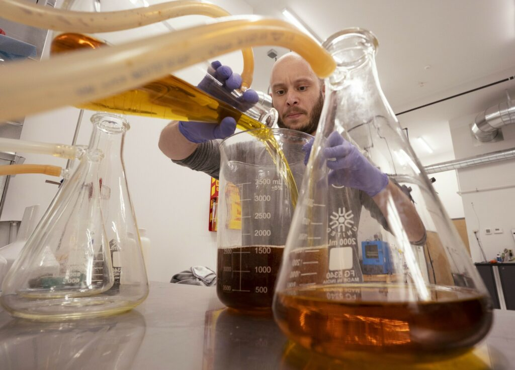Michael Scearce pours cannabis extract that just went through a  filtering processes at Governor's Island, a Portland business that extracts THC from cannabis for clients. The owners of the business, Janelle and Corey LaPlante, say it took a significant amount of money to set up the lab and not being able to do business with banks has made that process more difficult. Banks and credit unions are awaiting the outcome of a federal law that would provide safe harbor to financial institutions that provide banking services to cannabis industries in states where it has been legalized.