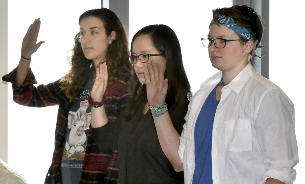 Colby College students, from left, Anna Braverman, Lutie Brown and Colleen George are sworn in to testify before the  Waterville Voter Registration Appeals board during a hearing in Waterville regarding voter eligibility on May 1. Their votes were challenged by opposers of the plastic bag ban in Waterville.