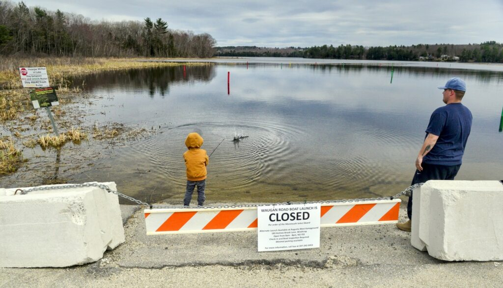 Noah Allen, 4, of Wales, left, casts into Annabessacook Lake as his father, Zachary Allen, watches Wednesday at the closed boat launch on Waugn Road in Monmouth.