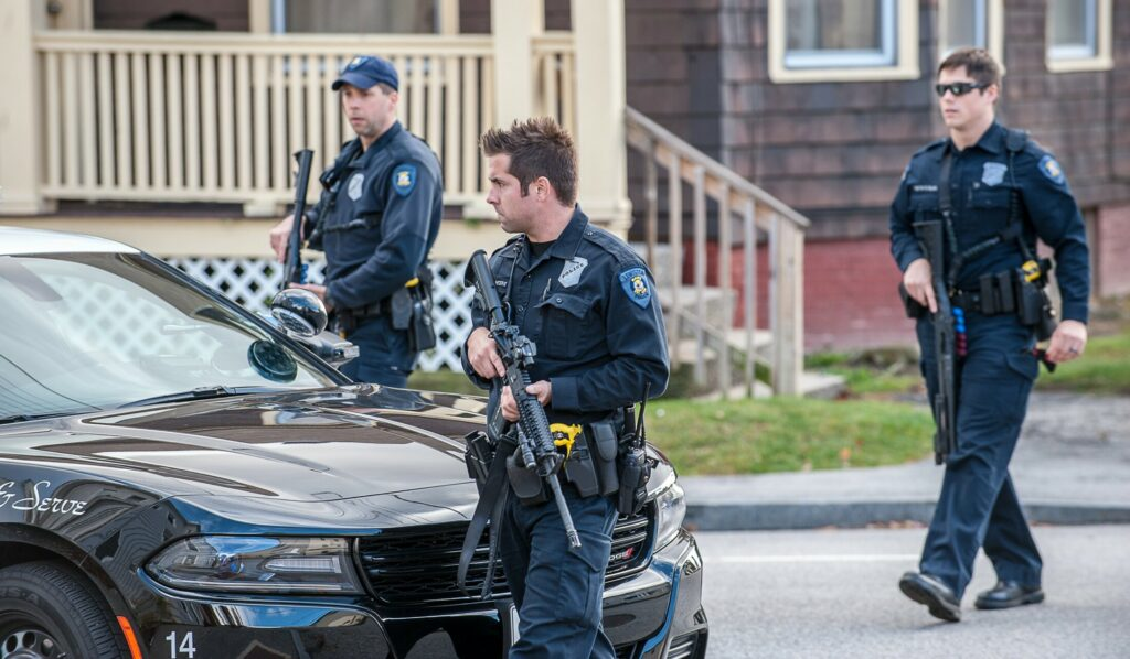 Officer Nicholas Meserve, center, and other Lewiston police officers search for a man who shot at a vehicle at the corner of Sabattus and College streets in 2016. Meserve's death in February has raised questions about whether municipalities require drug tests of employees.