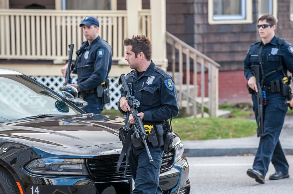 Officer Nicholas Meserve of the Lewiston Police Department crosses Ash Street in Lewiston with other officers as they walk down Howe Street while searching for a man who had shot at a vehicle in 2016. Meserve, 34, died at his home Feb. 8. from acute fentanyl intoxication, according to the Office of the Chief Medical Examiner.