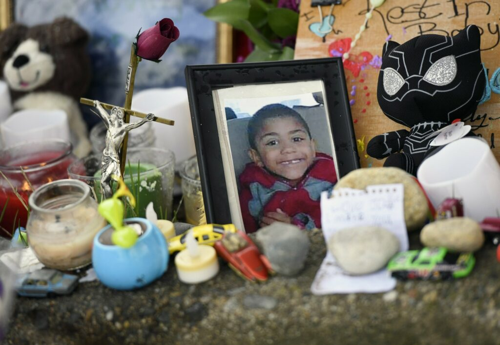 A photograph of Jayce Holt is placed at a makeshift memorial Thursday near where he was struck and killed by a school bus on the previous afternoon.