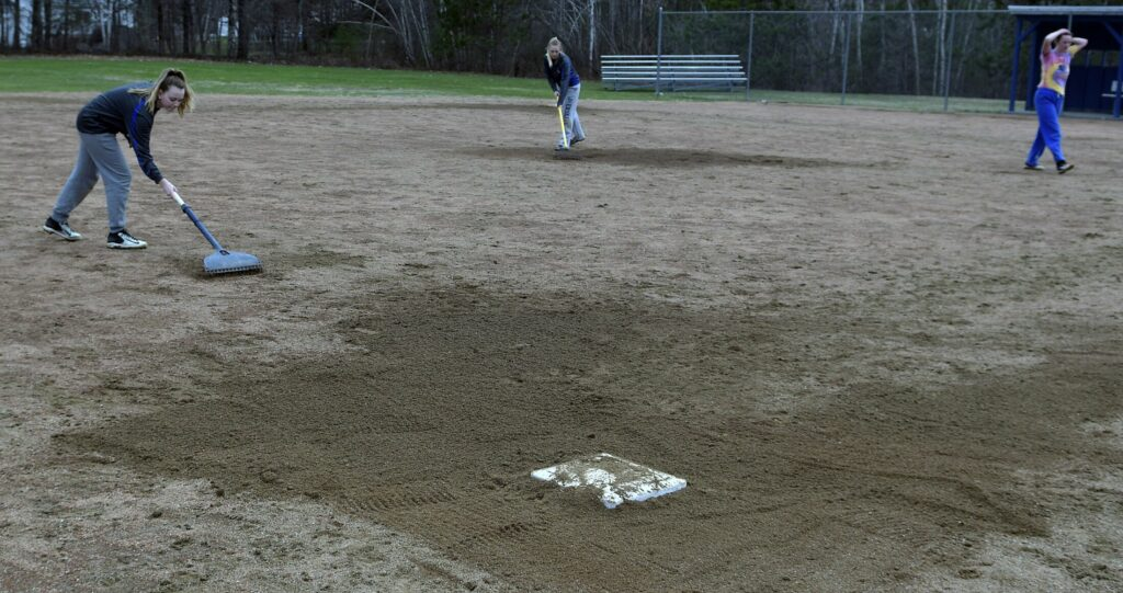 Erskine softball players groom the field Thursday in South China following practice.