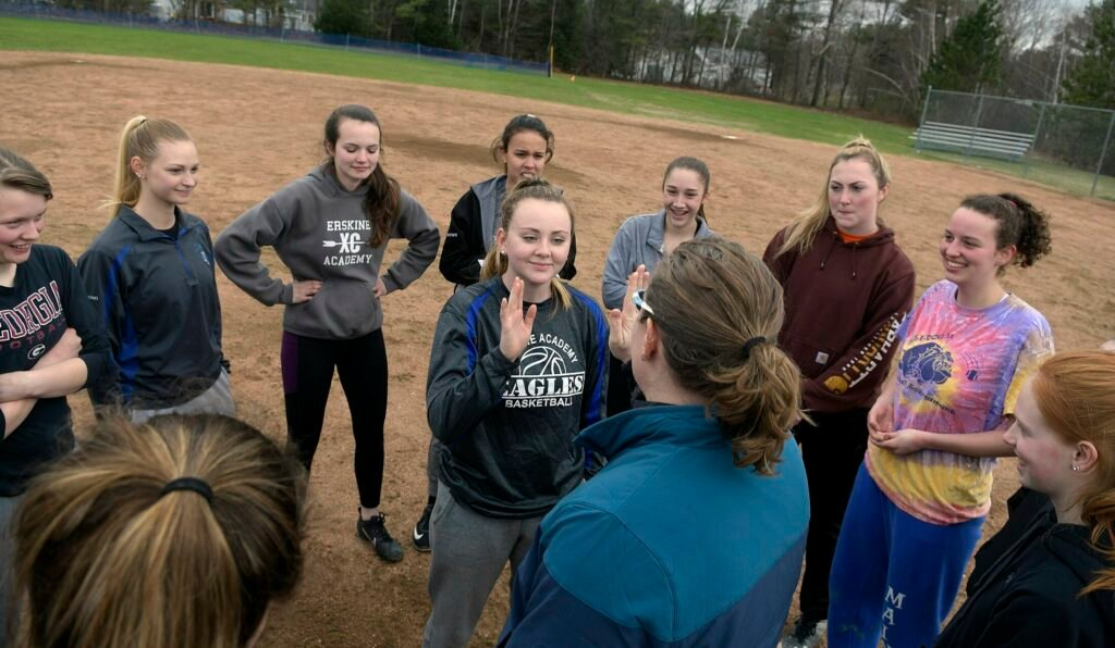 Erskine softball players gather in a circle and praise their teammate Parker King, center, following practice at the school Thursday in South China.