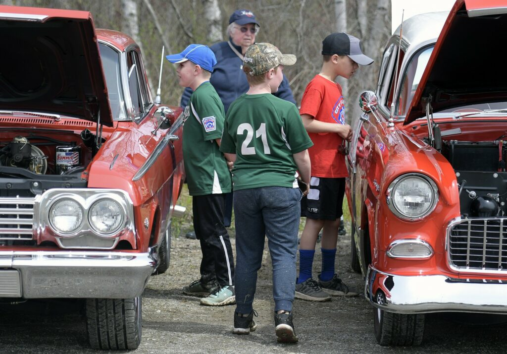 Baseball players inspect during the cruise in of cars Sunday at the CARA fields. A fundraiser was held to replace a concession stand at the complex destroyed by fire.