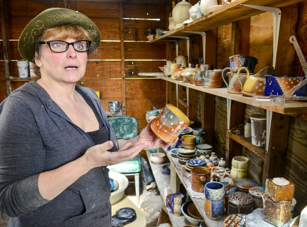 Lori Watts talks about pieces she took out of the kiln earlier in the morning Saturday during a Maine Pottery Tour event at Fine Mess Pottery in Augusta.
