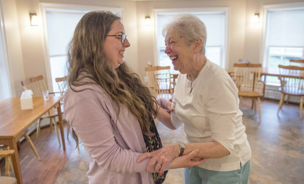 Abbie Hartford receives a hug and thanks from Nancy Barnes after morning exercises at the Pierce House in Farmington on Friday. The UMF graduating senior started UMF Senior Buddies to address the issue of loneliness among the elderly and to get students to visit them in group homes.